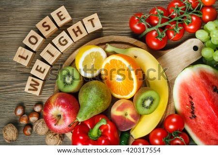 Diet concept. Natural products rich in vitamins as oranges, lemons, red pepper, kiwi, tomatoes, bananas, pears, apples, walnuts, watermelon, hazelnuts, peach and green grape - stock photo