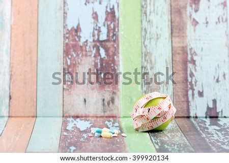 Diet concept with apple, measuring tape and pill medecine. Pallet texture background.Selective focus with shallow depth of field. - stock photo