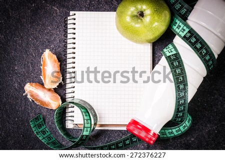 Diet concept with green apple, a notebook and a measuring tape