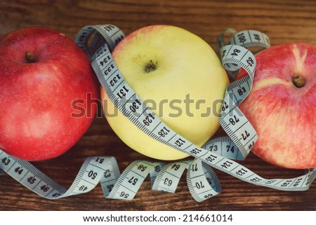 Diet concept with red and yellow apples and blue measuring tape on wooden table