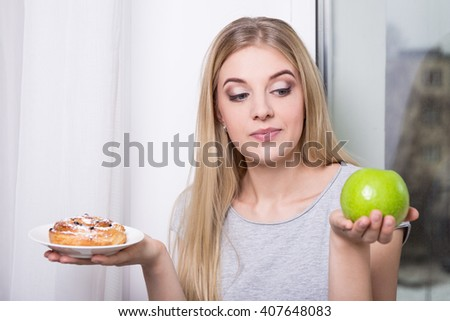 diet concept - young woman choosing behind pastry and green apple