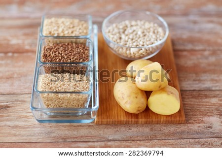diet, cooking, culinary and carbohydrate food concept - close up of grain and beans in glass bowls with potatoes on table - stock photo
