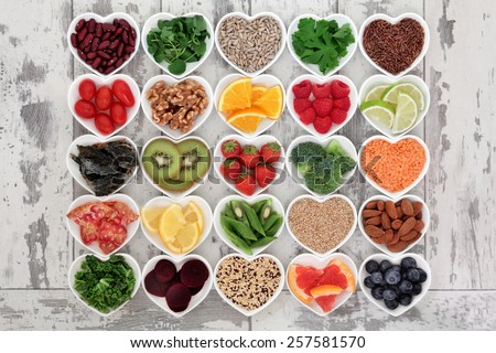 Diet detox super food selection in heart shaped porcelain bowls over distressed wooden background. - stock photo
