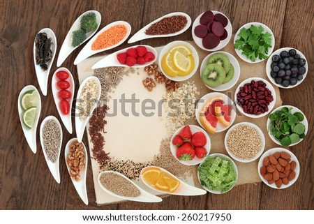 Diet detox super food selection in porcelain bowls on a speckled hemp paper notebook over oak wood background. - stock photo