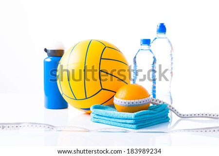 Diet diabetes weight loss concept with ball, tape measure, organic orange, towels and sprt bottle with bottles of natural sparkling water on a white background. - stock photo