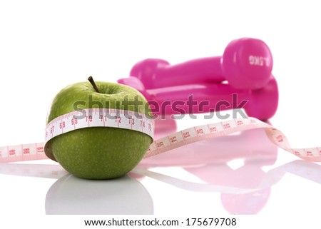 Diet diabetes weight loss concept with tape measure organic green apple and pink dumbbels on a white background. - stock photo