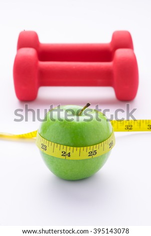 Diet diabetes weight loss concept with tape measure organic green apple and red dumbbels on a white background. Fitness care concept - stock photo