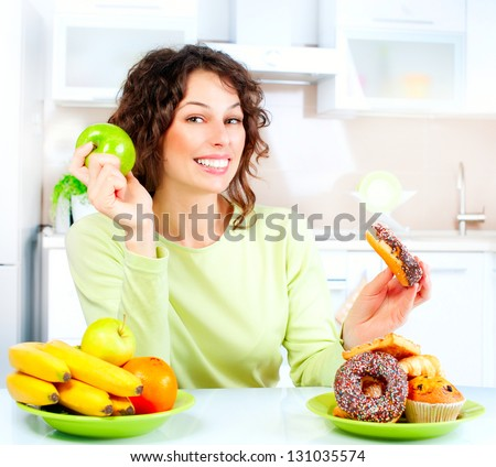 Diet. Dieting concept. Healthy Food. Beautiful Young Woman choosing between Fruits and Sweets. Weight Loss. Loosing Weight concept