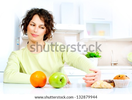 Diet. Dieting concept. Healthy Food. Beautiful Young Woman choosing between Fruits and Sweets - stock photo