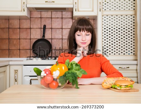 Diet. Dieting concept. Healthy Food. Beautiful Young Woman choosing between Vegetables and Fast Food. Weight Loss. - stock photo