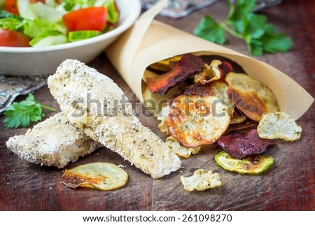Diet fish and vegetable crisps in paper, low-calorie tasty dish - stock photo
