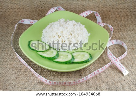 diet food. A handful of rice and cucumbers on the green plate on a rough burlap cloth - stock photo