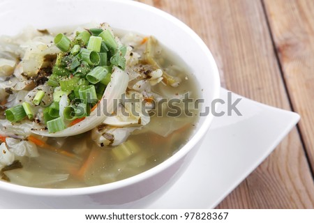 diet food : hot vegetable soup with bread  crackers in white bowl on  stand over wood table