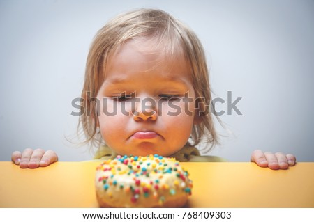 Diet for kids. sad and unhappy child Child reaches donuts. Tasty food for kids. Kid is looking on doughnut. junk food addiction.