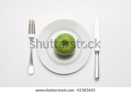 diet - green apple on a white plate with knife and fork