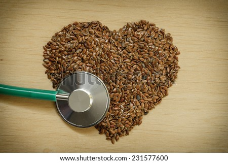 Diet healthcare and checkup concept. Raw flax seeds linseed heart shaped and stethoscope. Healthy food for preventing heart diseases. - stock photo