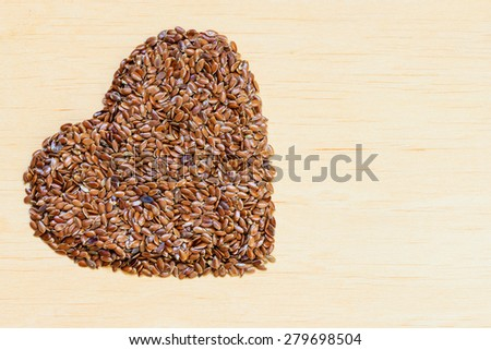 Diet healthcare concept. Raw flax seeds linseed heart shaped on wooden background. Healthy food for preventing heart diseases. - stock photo