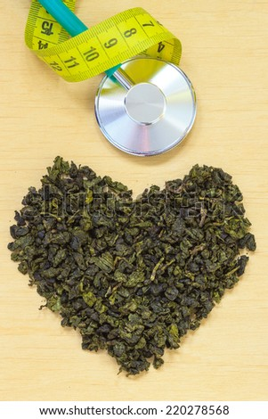 Diet healthcare weight loss concept. Green tea heart shaped stethoscope on wooden surface. Healthy food drink for lower heart disease risk - stock photo