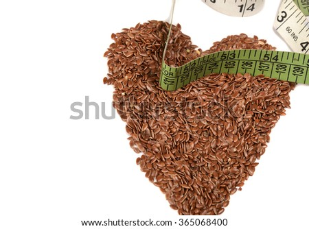 Diet healthcare weight reduction concept. Flax seeds linseed heart shaped with measuring tape. Healthy food for preventing heart diseases, overweight - stock photo