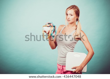 Diet, healthy eating and slim body concept. Fit fitness girl holding bowl with many colorful measuring tapes as dieting symbol and weight scales studio shot on blue - stock photo