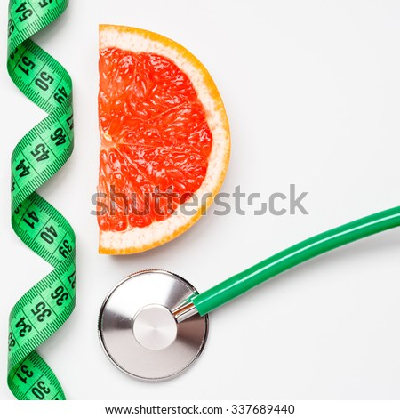 Diet healthy eating weight control concept. Grapefruit with measuring tape and stethoscope on white scales - stock photo