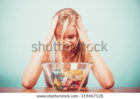 Diet, healthy eating, weight loss and slim body concept. Fit fitness girl and bowl with many colorful measuring tapes, young woman bored of dieting - stock photo