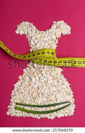 Diet healthy food slim body concept. Female dress shape made from oatmeal vegetables with measuring tape around thin waist on red - stock photo