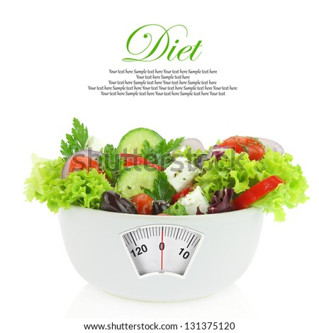 Diet meal. Vegetables salad in a bowl with weight scale - stock photo