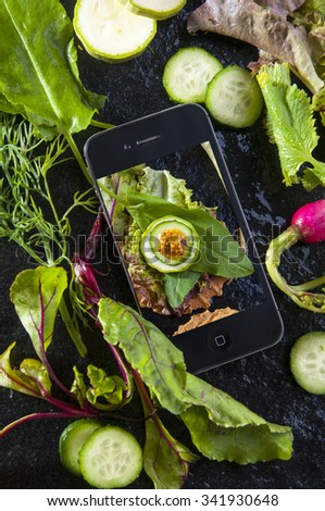 Diet menu. Food photo on smartphone with sandwich. Fresh herbs and vegetables around mobile phone, top view - stock photo