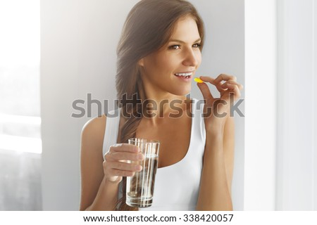 Diet. Nutrition. Healthy Eating, Lifestyle. Close Up Of Happy Smiling Woman Taking Pill With Cod Liver Oil Omega-3 And Holding A Glass Of Fresh Water In Morning. Vitamin D, E, A Fish Oil Capsules.