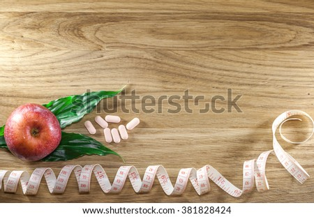 Diet pills and apple on wooden background. The concept of diet, health - stock photo