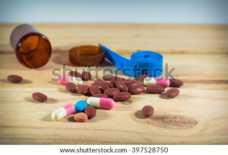 diet pills with blue measuring tape on wooden background - stock photo