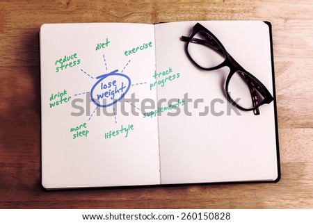 Diet plan against overhead of reading glasses with notebook - stock photo