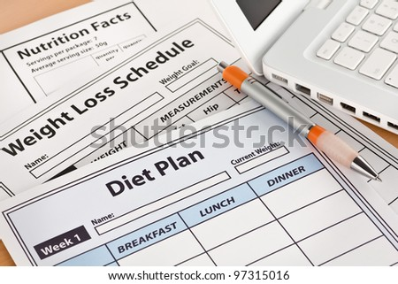 Diet Plan and Weightloss Schedule by Laptop on Table - stock photo