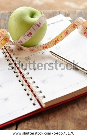 Diet plan concept,Green apple with measuring tape ,calendar and pen