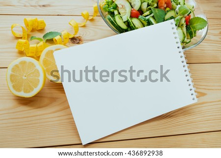 Diet plan, menu or program, lemon, tape measure and diet food of fresh salad on wood background, weight loss and detox concept, top view - stock photo