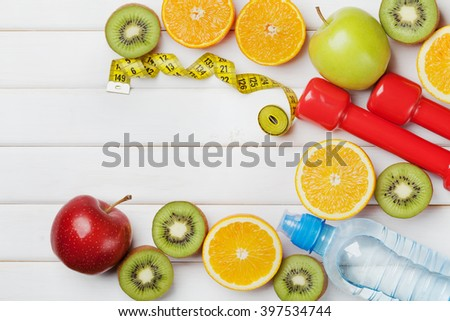 Diet plan, menu or program, tape measure, water, dumbbells and diet food of fresh fruits on white background, weight loss and detox concept, top view