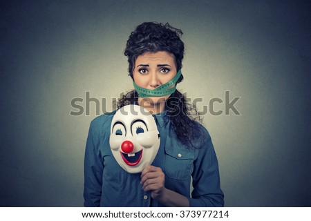 Diet restriction and stress concept. Portrait of young sad woman with clown mask and  measuring tape around her mouth isolated on gray wall background. Unhappy face expression emotion  - stock photo