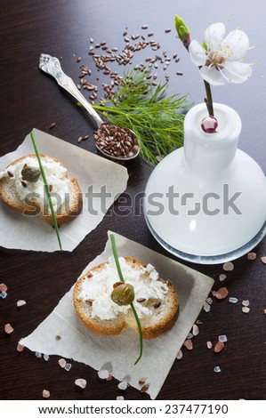 Diet sandwiches with cheese curds and capers, flax seeds, dill and vase with apricot flower - stock photo