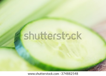 diet, vegetable food and objects concept - close up of cucumber slices and celery - stock photo