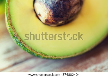 diet, vegetable food and objects concept - close up of ripe avocado cut with bone on table - stock photo