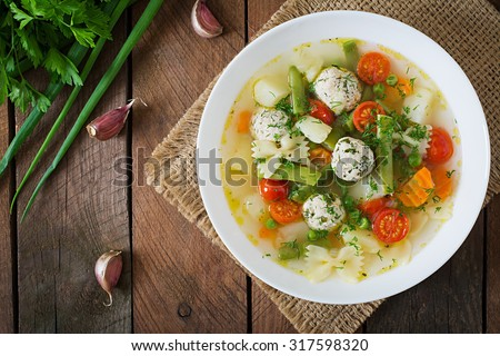 Diet vegetable soup with chicken meatballs and fresh herbs in bowl. Top view - stock photo