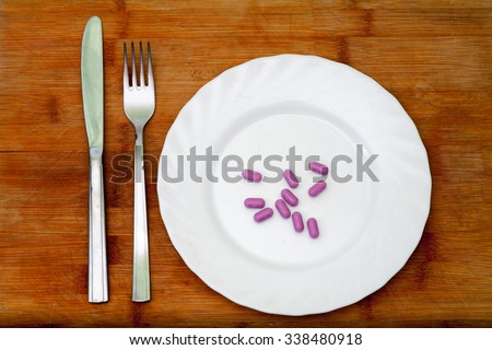 Diet. Violet pills on round white plate and fork with knife - stock photo