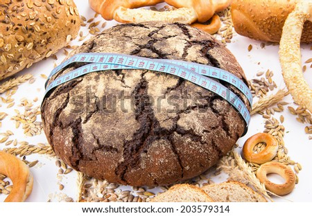 Diet weight gain concept. Fresh bread with tape over white background - stock photo