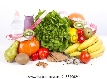 Diet weight loss breakfast concept - organic green salad, pears, grapefruit, tomatoes. pumpkin, quail eggs, nuts, yogurt, water - healthy food. Measurement measuring tape - stock photo
