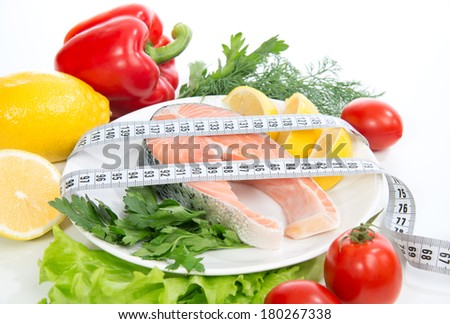 Diet weight loss concept. Fresh salmon steak for lunch with tape measure centimetr - stock photo