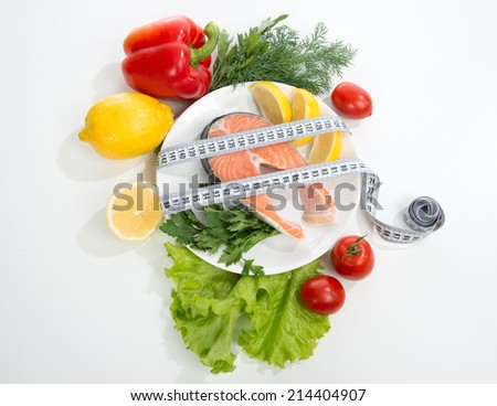 Diet weight loss concept. Fresh salmon steak for lunch with tape measure centimetr lemon tomatoes on a white background