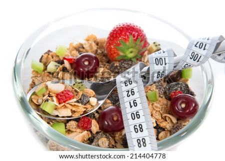 Diet weight loss concept tape measure spoon muesli cereals bowl almond, pine nuts, walnut, raisins, oat and wheat flakes, fresh fruits kiwi, strawberry pieces pomegranate seeds - stock photo