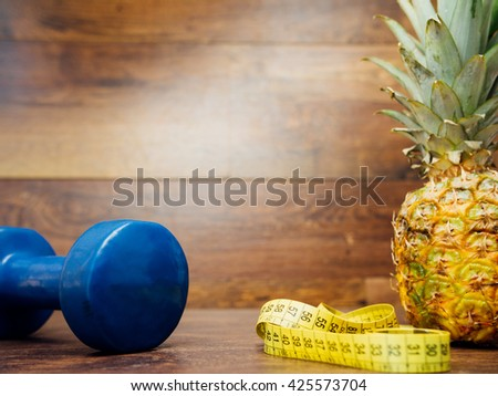 Diet weight loss fitness health care concept with dumbbell, pineapple, measure tape on wood background. Diet heathy sport fitness healthcare workout items. Measure tape metric ribbon and dumbbell. - stock photo