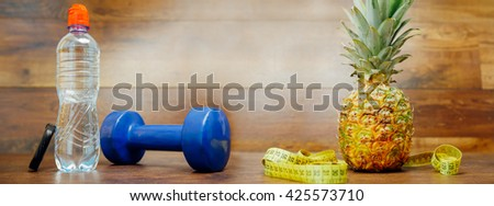Diet weight loss fitness health care concept with measure tape, pineapple, water bottle, fitness dumbbell, fitness tracker bracelet. Pineapple, metric ribbon on wood background. Diet heathy panorama. - stock photo